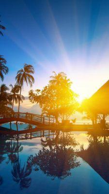عکس زمینه طلوع خورشید لب ساحل و آلاچیق