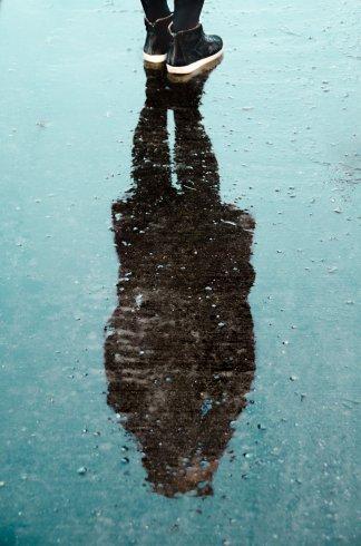 عکس زمینه سایه شخص روی سطح آب زمین بارانی