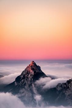 عکس زمینه قله کوه میان ابر در افق طلوع صبح
