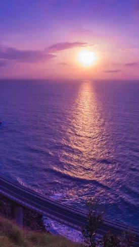 عکس زمینه غروب خورشید آسمان در دریای بنفش رنگ