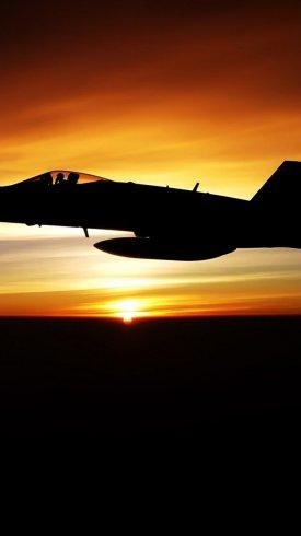عکس زمینه پرواز جنگنده نظامی در غروب آفتاب