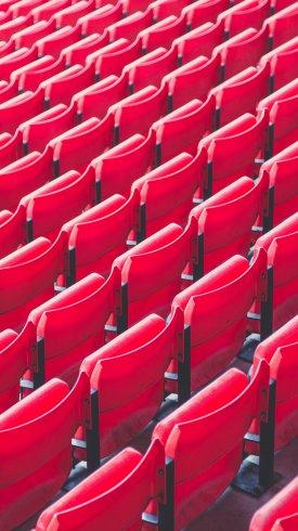عکس زمینه صندلی قرمز رنگ خالی استادیوم