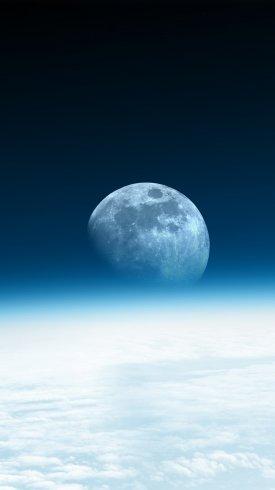 عکس زمینه نمایی از ماه با افق آبی بالای ابرها