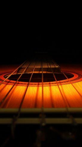عکس زمینه گیتار چوبی با پس زمینه تاریک