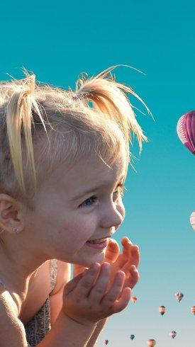عکس زمینه دختر ناز شاد با بادکنک در هوای گرم
