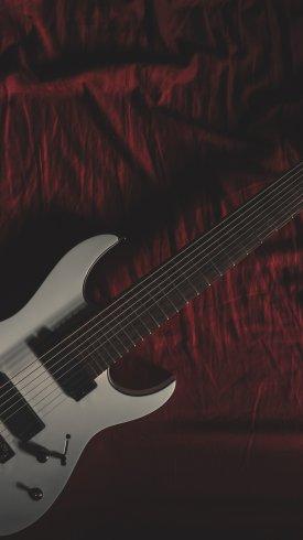 عکس زمینه گیتار سفید بر روی تخت