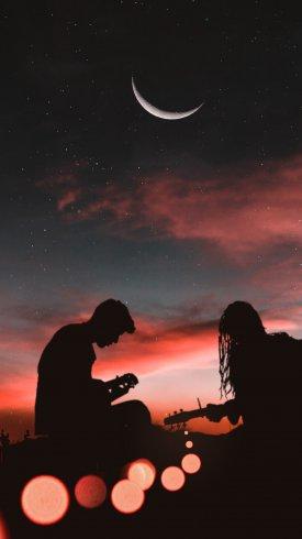 عکس زمینه پسر و دختر در حال نواختن گیتار در شب